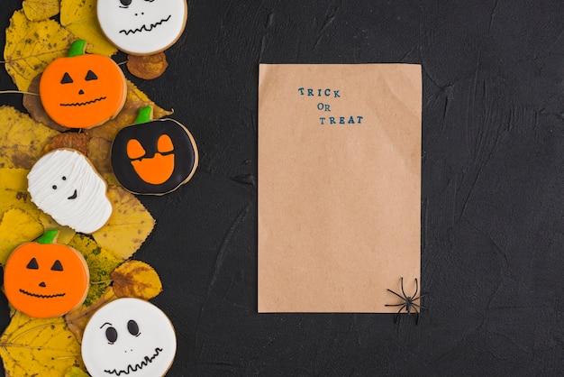 Carta artigianale con ragno vicino a biscotti e foglie di halloween