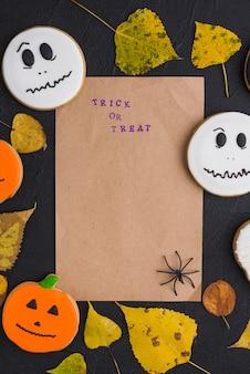 Carta artigianale vicino a pan di zenzero, foglie e ragno