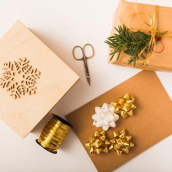 Carta artigianale vicino a prua, scatole regalo, forbici, ornamento fiocco di neve e nastro