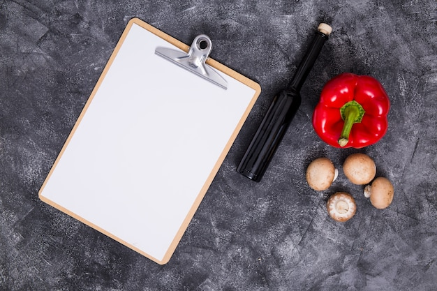 Carta bianca bianca su appunti con peperone; fungo e bottiglia su sfondo nero con texture