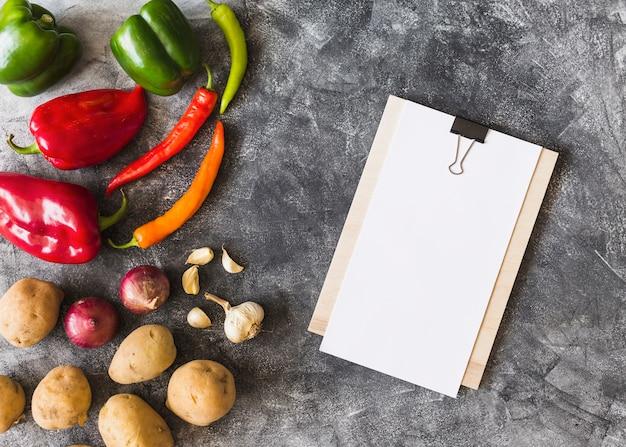 Carta bianca bianca sulla lavagna per appunti con le verdure sulla priorità bassa del grunge