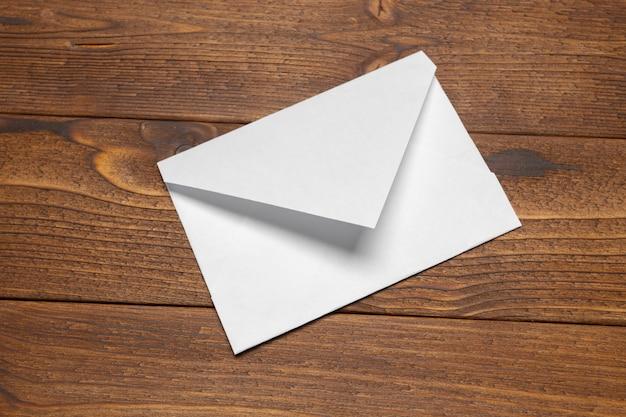 Carta bianca, busta sul tavolo di legno