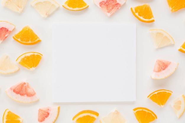 Carta bianca circondata con fette di agrumi colorati su sfondo bianco