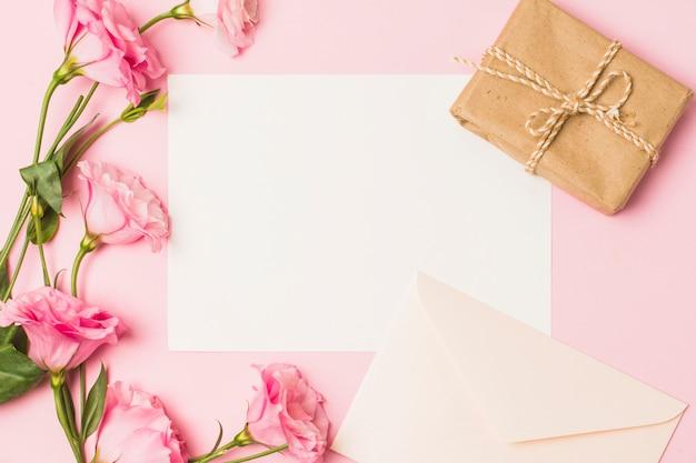 Carta bianca con busta; fiore rosa fresco e scatola regalo avvolto marrone su sfondo rosa