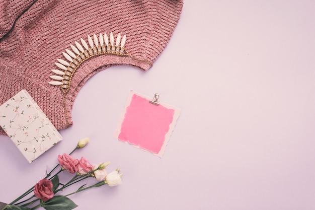 Carta bianca con fiori di rosa, collana e maglione sul tavolo