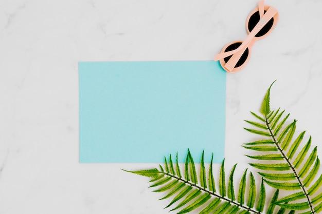 Carta bianca con occhiali da sole sulla superficie chiara