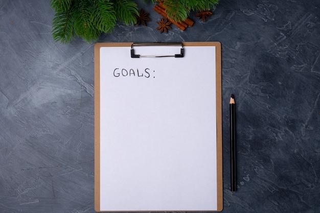 Carta bianca con titolo di obiettivi e matita nera sul tavolo grigio.