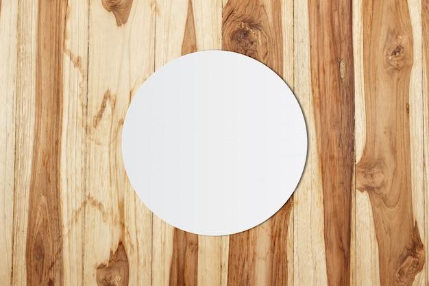 Carta bianca del cerchio e spazio per testo su fondo di legno
