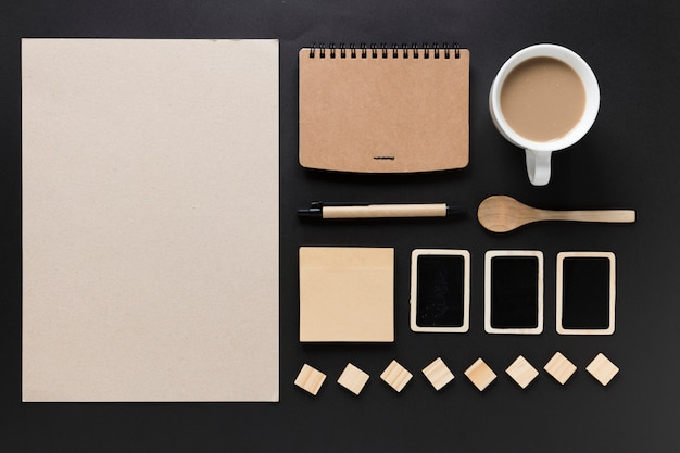 Carta bianca; diario; tazza di tè; cucchiaio; nota adesiva; carte e blocchi su sfondo nero