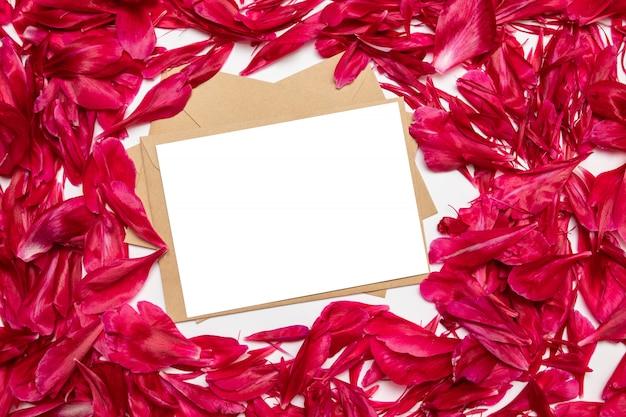 Carta bianca e busta con petali di peonie rosse su grigio