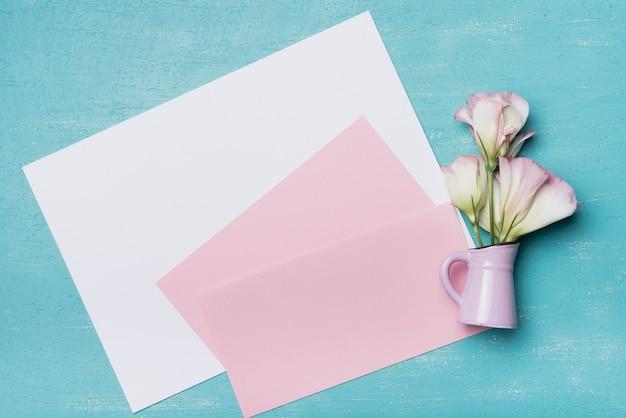 Carta bianca e rosa in bianco con il vaso di eustoma contro il contesto blu