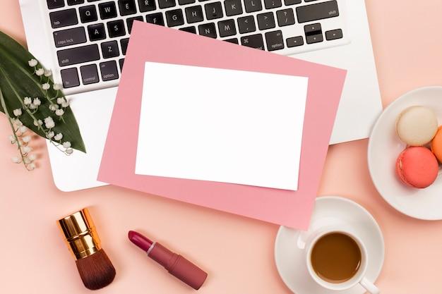 Carta bianca e rosa vuota sul portatile con rossetto, pennello per trucco e tazza di caffè con amaretti sopra la scrivania