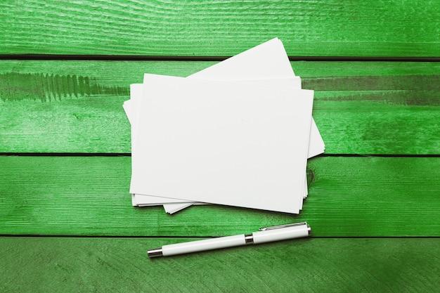 Carta bianca, penna e busta sul tavolo di legno verde