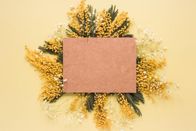 Carta bianca sui rami di fiori gialli