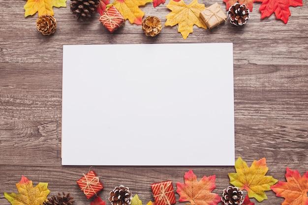 Carta bianca vista dall'alto con foglie di acero colorate, coni, scatole regalo minuscole su superficie di legno
