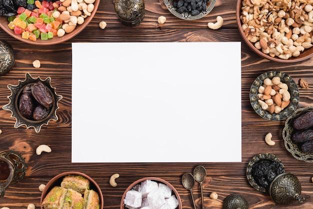 Carta bianca vuota circondata da frutta secca mista; date; lukum; baklava e noci sulla scrivania in legno per il ramadan