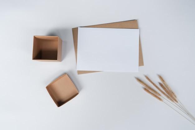 Carta bianca vuota su busta di carta marrone con fiore secco di coda di volpe ispida e scatola di cartone. vista dall'alto della busta artigianale su sfondo bianco.
