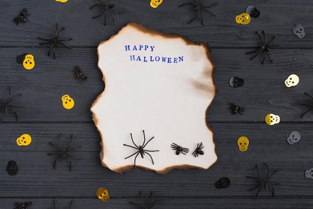 Carta bruciata con decorare ragni e teschi