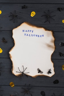 Carta bruciata vicino a decorare ragni e teschi