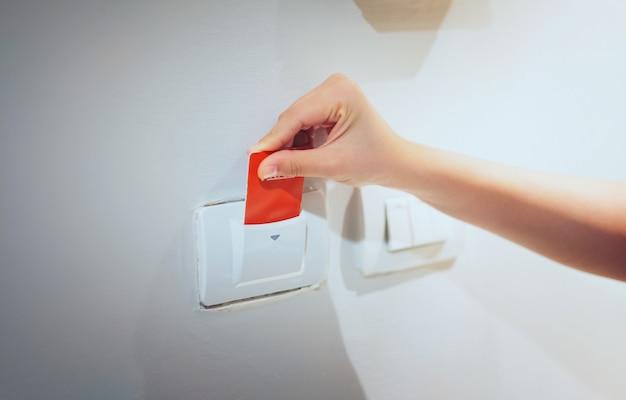 Carta chiave dell'inserzione della mano delle donne del primo piano a luce elettronica di apertura nella camera di albergo.