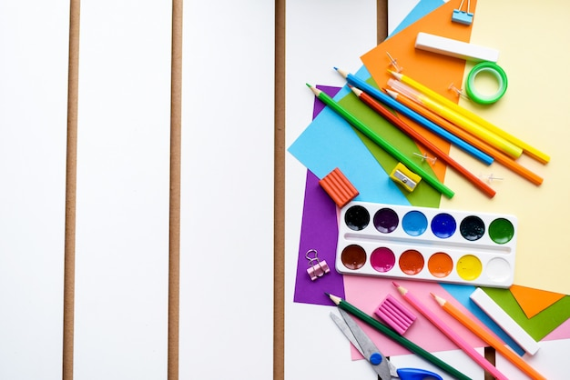 Carta colorata e cancelleria su uno sfondo bianco