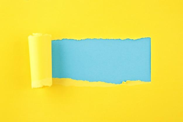 Carta colorata strappata, buco nel foglio di carta sullo sfondo