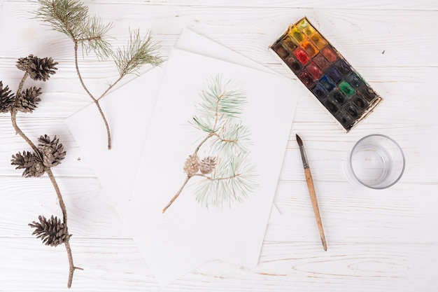 Carta con pittura vegetale vicino a vetro, pennello, ramoscelli e acquerelli