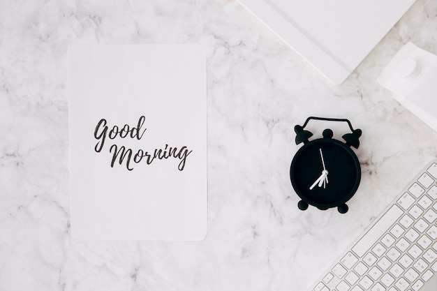 Carta con testo del buongiorno; sveglia; diario; scatola di latte e tastiera sulla scrivania