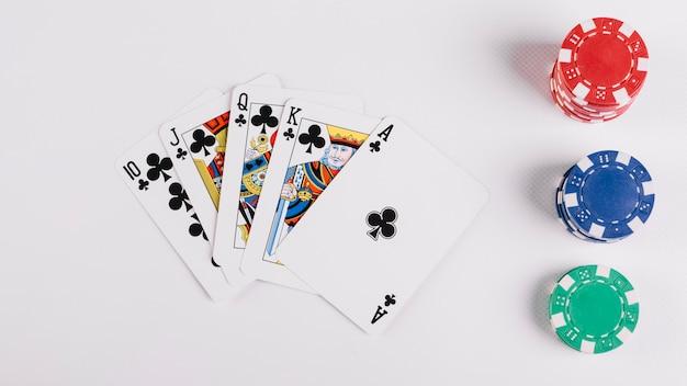 Carta da gioco con club royal flush e fiches del casinò su sfondo bianco