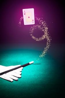 Carta da gioco in aria con un paio di guanti bianchi e bacchetta su sfondo colorato