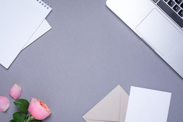 Carta da parati grigia con carta regalo, rosa rosa e laptop