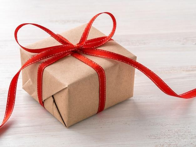 Carta da regalo marrone kraft avvolgente, con nastro rosso sul tavolo di legno bianco, vista laterale