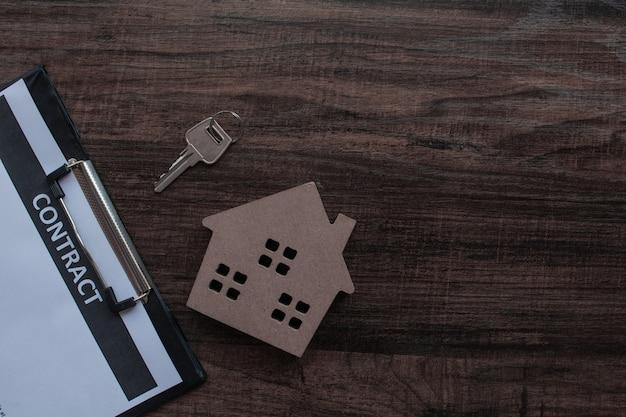 Carta del contratto e del bene immobile con la chiave della casa sulla tavola di legno