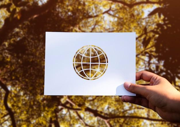 Carta del globo della tenuta della mano che scolpisce con il fondo della natura