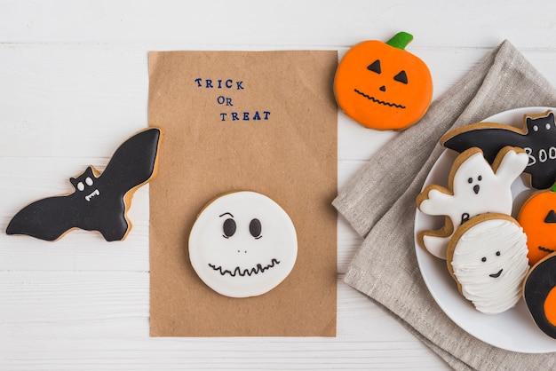 Carta del mestiere intorno al pan di zenzero e ai biscotti di halloween sul piatto