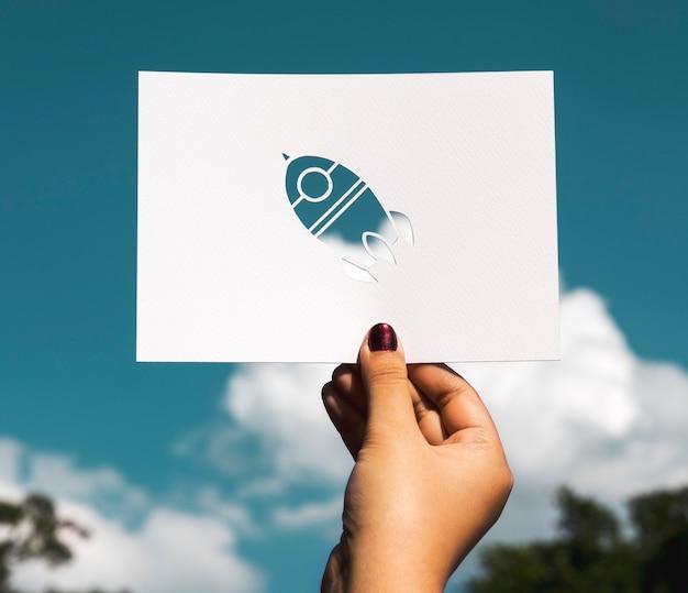 Carta del razzo di spazio della tenuta della mano che scolpisce con il fondo del cielo
