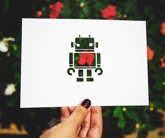 Carta del robot della tenuta della mano che scolpisce con il fondo della natura