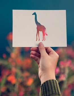 Carta della giraffa della tenuta della mano che scolpisce con il fondo del fiore