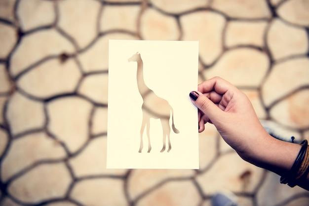 Carta della giraffa della tenuta della mano che scolpisce con il fondo incrinato