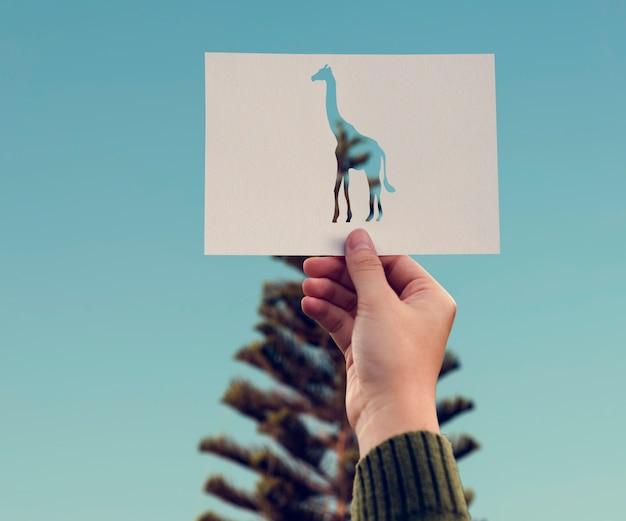 Carta della giraffa della tenuta della mano che scolpisce con l'albero di pino