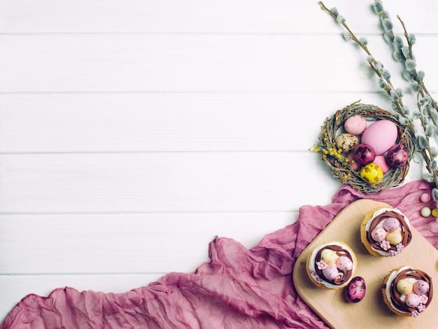 Carta di buona pasqua con cupcakes nido, uova dipinte e brunch fioriti di salice