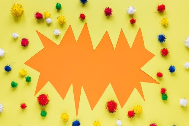 Carta di carnevale ritagliata con pompon colorati