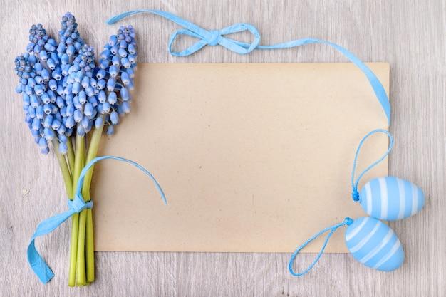 Carta di carta bianca incorniciata da uova di pasqua e giacinto di uva, spazio del testo