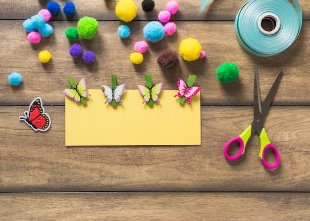 Carta di carta gialla decorata con farfalle su fondo in legno