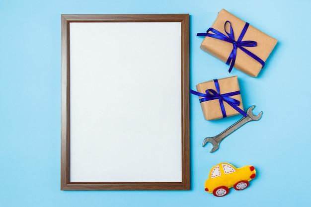 Carta di concetto di festa del papà con lo strumento del lavoro dell'uomo su fondo blu e contenitori di regali avvolti in carta kraft e legati con l'arco blu.