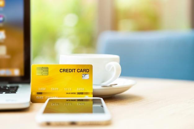 Carta di credito della tazza del computer portatile, dello smartphone e di caffè su legno
