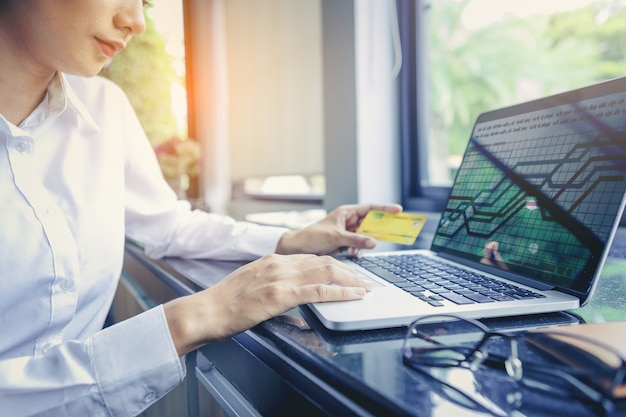 Carta di credito della tenuta della donna di affari e computer portatile usando. acquisti online . focus selezionato