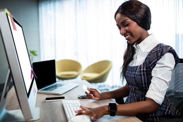 Carta di credito della tenuta della donna di affari e scrivere sul computer