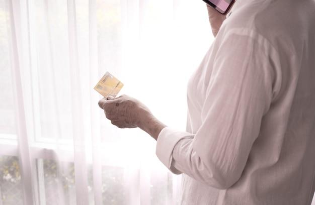 Carta di credito della tenuta della donna di affari e telefono usando sulla tenda bianca