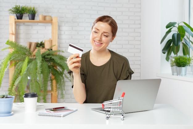 Carta di credito della tenuta della giovane donna e computer portatile usando.